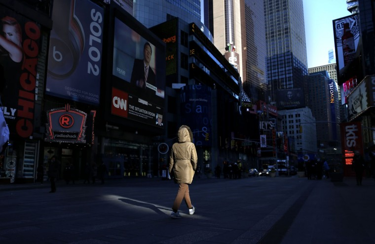 A woman bundled up against the cold weather walks through a mostly empty Times Square, Thursday, Jan. 8, 2015, in New York. Dangerously cold air has sent temperatures plummeting into the single digits around the U.S., with wind chills driving them even lower. (AP Photo/Seth Wenig)