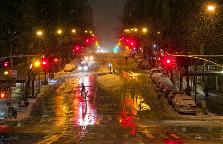 A person crosses a snow-covered street in the Upper West Side neighborhood of New York, Monday, Jan. 26, 2015. People in the Northeast by the thousands prepared for a snowstorm that could be one for the history books, with some 35 million people in its path in the Philadelphia-to-Boston corridor. (AP Photo/Craig Ruttle)