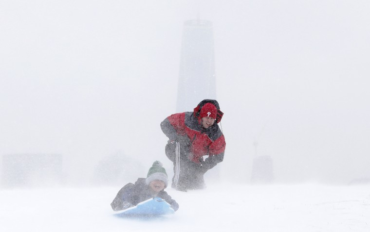 Rick Caso, center, watches as his son Andrew sleds down a hill, with One World Trade Center obscured in the background, at Liberty State Park, Monday, Jan. 26, 2015, in Jersey City, N.J. The Philadelphia-to-Boston corridor of more than 35 million people began shutting down as a monster storm, that could unload a paralyzing 1 to 3 feet of snow, moved through the northeast. (AP Photo/Julio Cortez)
