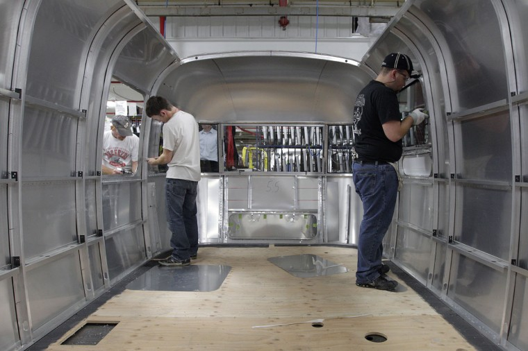 Russell Hites, left, of Belle Center, and Charlie Presne, of Uniopolis, work on an Airstream travel trailer at the Airstream factory Wednesday, Oct. 22, 2014, in Jackson Center, Ohio. (AP Photo/Jay LaPrete)