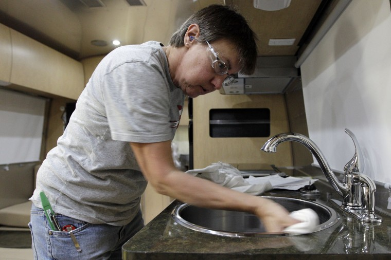 Lisa Poppe, of Jackson Center, cleans the kitchen area of an Airstream travel trailer at the Airstream factory Wednesday, Oct. 22, 2014, in Jackson Center, Ohio. (AP Photo/Jay LaPrete)