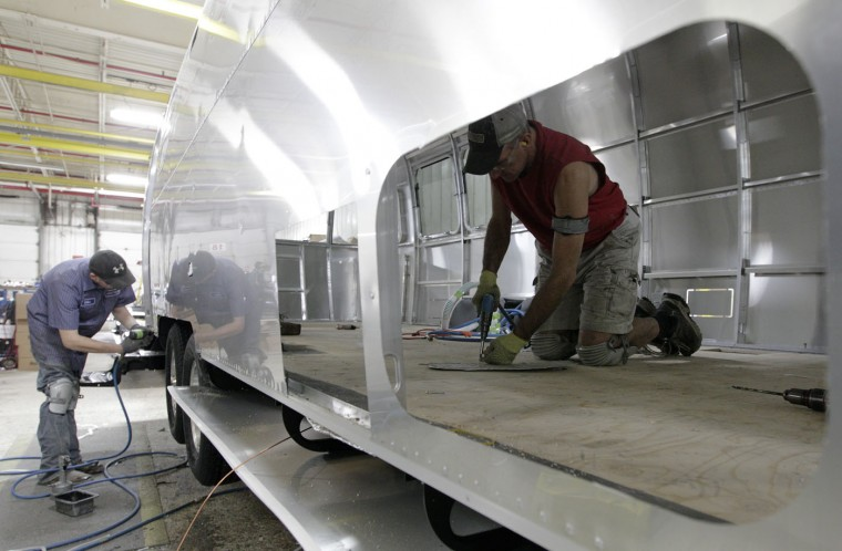 In this Oct. 22, 2014 photo, Michael Shaw, left, of Rushylvania, Ohio, and Gary Kesler, of Elida, Ohio, work on an Airstream travel trailer at the Airstream factory in Jackson Center, Ohio. Not only are the Airstream trailers still being built by hand at the same western Ohio site that has produced them for the past 60 years, but the company also can't roll them out of there fast enough to meet the demand these days. (AP Photo/Jay LaPrete)