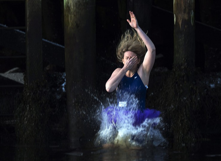 A woman plugs her nose as she leaps from the government wharf into the frigid North Atlantic in the annual New Year's Day polar bear swim in Herring Cove, Nova Scotia, Canada, on Thursday, Jan. 1, 2015. (Andrew Vaughan/AP Photo/The Canadian Press)