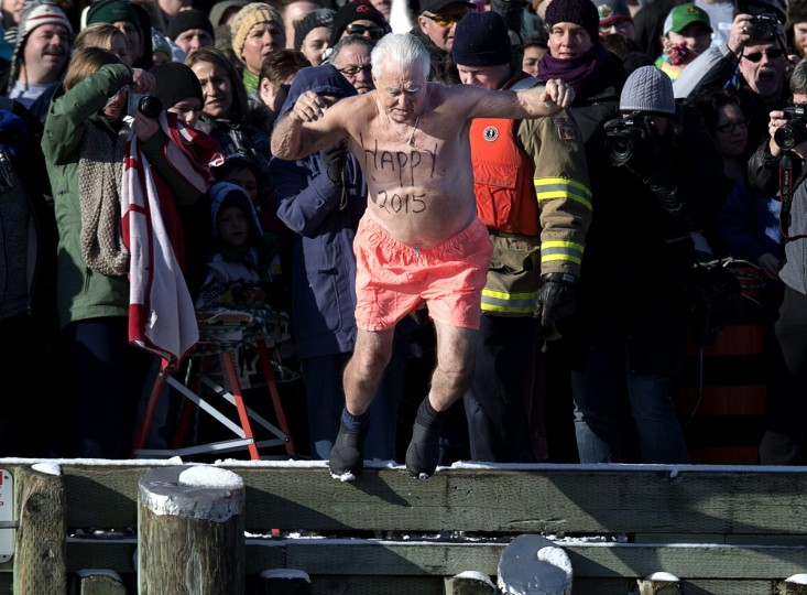 Ernie Ross, 80, welcomes the new year as he leaps from the government wharf into the frigid North Atlantic in the annual New Year's Day polar bear swim in Herring Cove, Nova Scotia, on Thursday, Jan. 1, 2015. (Andrew Vaughan/AP Photo/The Canadian Press)