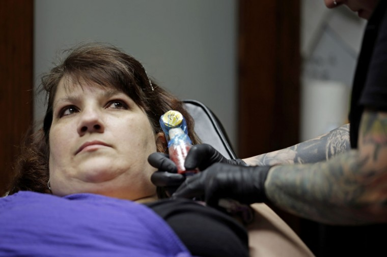 In this photo taken Wednesday, Dec. 17, 2014, tattoo artist Ashley Neumann tattoos over a scar on breast cancer survivor Mari Jankowski in West Allis, Wis. (AP Photo/Morry Gash)