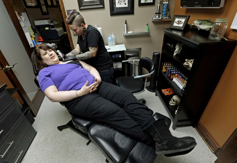 "In this Wednesday, Dec. 17, 2014 photo, tattoo artist Ashley Neumann tattoos over a scar on breast cancer survivor Mari Jankowski in West Allis, Wis. Neumann, 24, had worked with cancer scars before. ""It's definitely something you want to nail for them because you know that means so much to them,"" she said. (AP Photo/Morry Gash)"