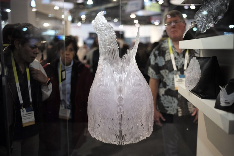 Attendees look at a 3D-printed dress by Iris van Herpen at the 3D Systems booth at the International CES Wednesday, Jan. 7, 2015, in Las Vegas. (AP Photo/Jae C. Hong)