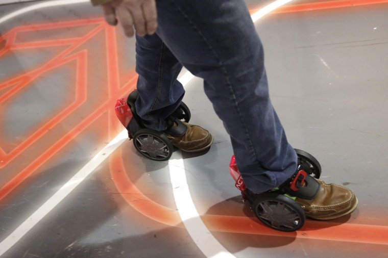 An attendee tries out a pair of RocketSkates at the Acton booth at the International CES Thursday, Jan. 8, 2015, in Las Vegas. (AP Photo/Jae C. Hong)