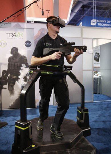 Christian Martin uses the Omni by Virtuix virtual treadmill during the International CES Wednesday, Jan. 7, 2015, in Las Vegas. The curved surface and special shoes allow the user to walk in place and sensors transform that into foreword motion in a virtual reality video game. (AP Photo/John Locher)