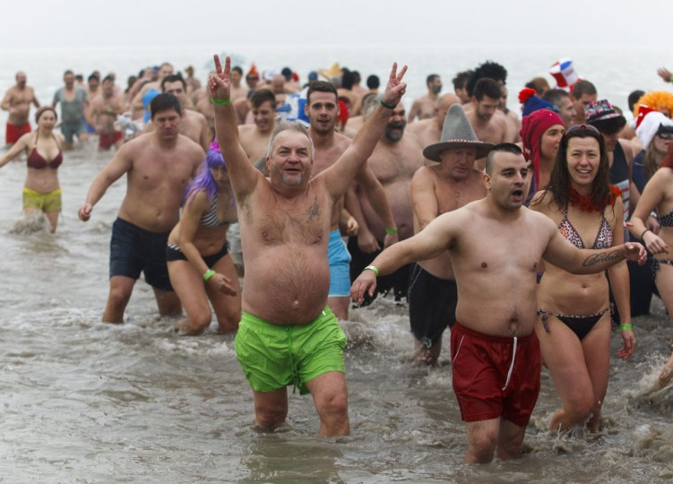 People run into the chilly water of Lake Balaton during the fourth annual New Year's swim in Szigliget, 164 kms southwest of Budapest, Hungary, Thursday, Jan. 1, 2015. (Gyorgy Varga/AP Photo/MTI)
