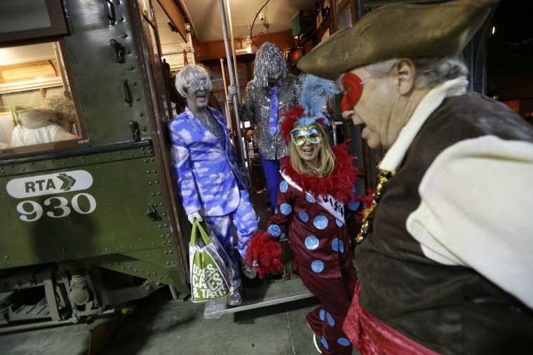 Members of the Phunny Phorty Phellows disembark a streetcar during their night of revelry in New Orleans, Tuesday, Jan. 6, 2015. King's Day is a tradition marking the 12th night after Christmas and the official start of the Mardi season. Carnival is celebrated along the Gulf Coast with parties, balls and parades culminating on Mardi Gras, or Fat Tuesday, a final day of celebration before Lent. It is a major tourist draw in New Orleans. Mardi Gras falls on Feb. 17 this year. (AP Photo/Gerald Herbert)