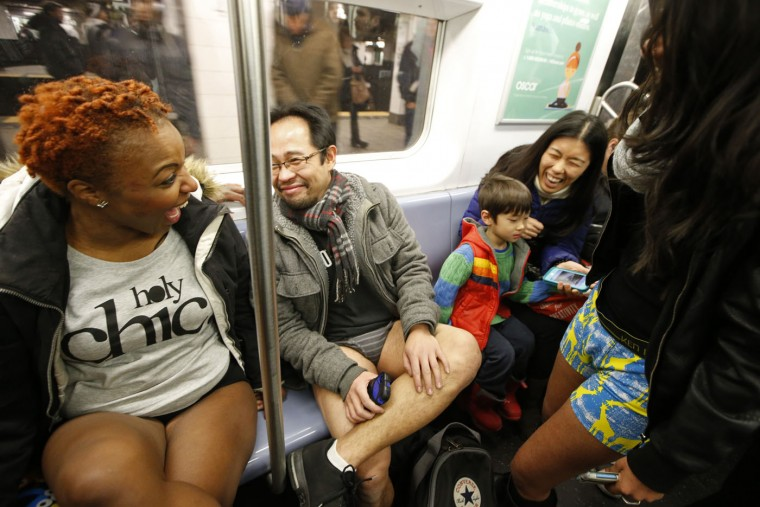 A woman riding the subway with her son laughs after realizing she encountered the annual No Pants Subway Ride, Sunday, Jan. 11, 2015, in New York. The No Pants Subway Ride began in 2002 in New York as a public prank and has since been celebrated by commuters around the world. (AP Photo/Kathy Willens)