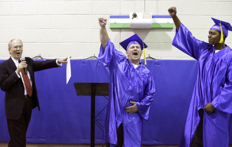 In this photo taken Dec. 12, 2014, Prison Entrepreneurship Program, or PEP, CEO Bert Smith, left, names Casey Allen, center, the winner of the business plan contest as second-place winner Jamaal Givens looks on during graduation ceremonies at the Cleveland Correctional Facility in Cleveland, Texas. (AP Photo/Pat Sullivan)