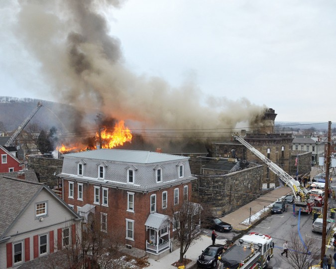 Flames shoot through the roof of the Northumberland County Prison in Sunbury, Pa., Wednesday, Jan. 14, 2015. Dispatchers say the blaze was reported just after 2 p.m. at the nearly 140-year-old jail in the city of 10,000 about 40 miles north of Harrisburg, Pa. (AP Photo/The Daily Item, Justin Engle)