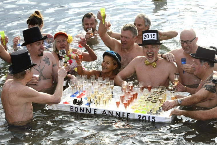 People celebrate with glasses of champagne in the cold water of Lake Geneva during the traditional New Year's swim, in Geneva, Switzerland, Thursday, Jan. 1, 2015. Around 70 swimmers took part in the 21st edition of the traditional bath to mark the New Year. (Keystone, Martial Trezzini/AP Photo)