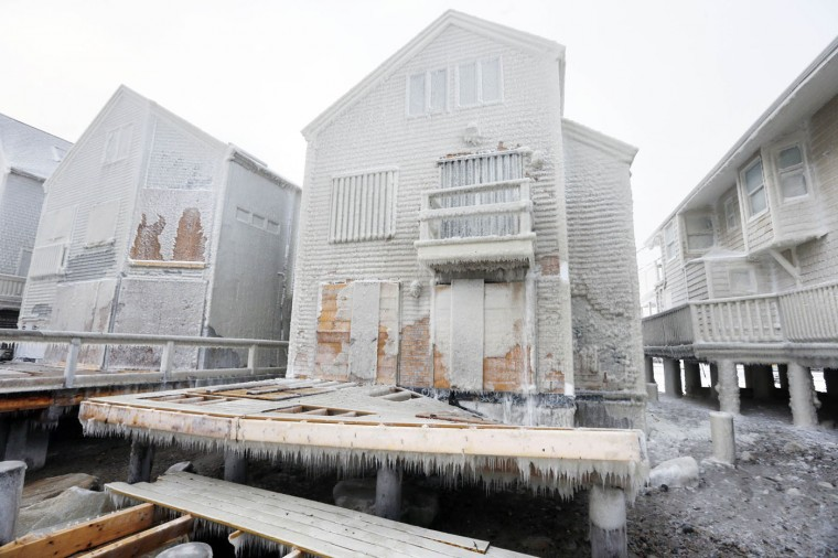 Frozen sea spray coats a house with a damaged deck the day after a winter storm in Scituate, Mass., Wednesday, Jan. 28, 2015. Residents of Massachusetts woke up Wednesday to cars buried in several feet of snow, and secondary roads that remain covered. (AP Photo/Michael Dwyer)