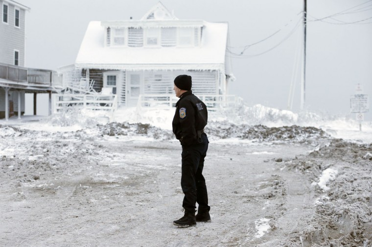 A police officer surveys the scene in Scituate, Mass., Wednesday, Jan. 28, 2015, the day after a winter storm deposited sand and rocks on the road and coated houses in frozen sea spray. The storm buried the Boston area in more than 2 feet of snow and lashed it with howling winds that exceeded 70 mph. (AP Photo/Michael Dwyer)