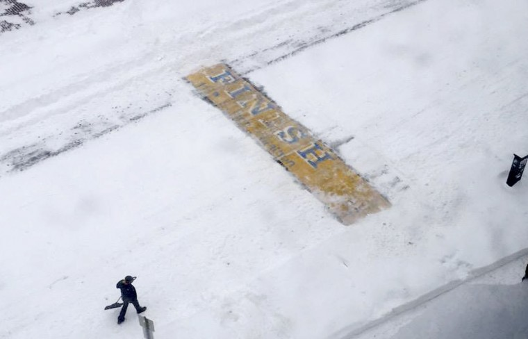 In this Tuesday, Jan. 27, 2015, photo, provided by Philip L. Hillman, Chris Laudani, a bartender at the Back Bay Social Club, pauses after shoveling snow from the Boston Marathon finish line on Boylston Street, in Boston, during a winter storm that slammed eastern Massachusetts with as much as 2 feet of snow. (AP Photo/Philip L. Hillman)