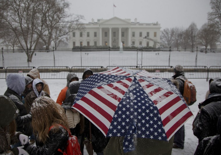 A light snow falls on a tour group outside the White House in Washington, Tuesday, Jan. 6, 2015, as temperatures hover around freezing. (AP Photo/Carolyn Kaster)