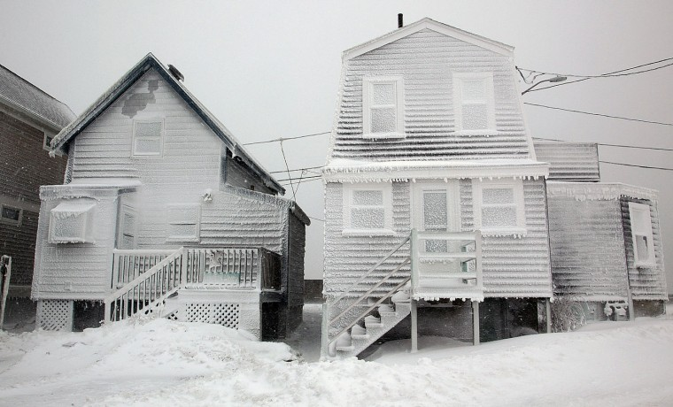 Frosted homes are battered by wind in Hull, Mass., Tuesday, Jan. 27, 2015. Massachusetts was pounded by snow and lashed by strong winds early Tuesday as bands of heavy snow left some towns including Sandwich on Cape Cod and Oxford in central Massachusetts reporting more than 18 inches of snow. (AP Photo/The Quincy Patriot Ledger, Gary Higgins)