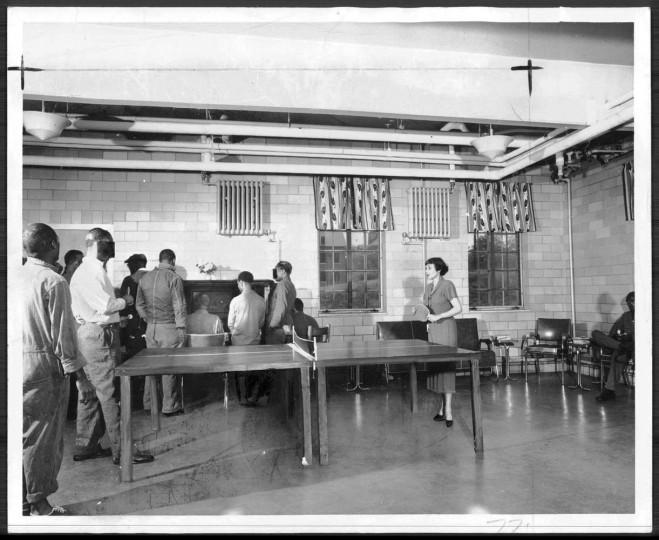 Patients at Crownsville State Mental Hospital enjoy a mid afternoon hour in the day room of their new pre parole ward which was furnished last week by the Townsmen e Progressive Club Inc. Here Miss Myra Blaustein eo ordinator of volunteer activities for the hospital plays ping pong with a patient while others gather to sing at the piano. Photo taken September 8, 1950.