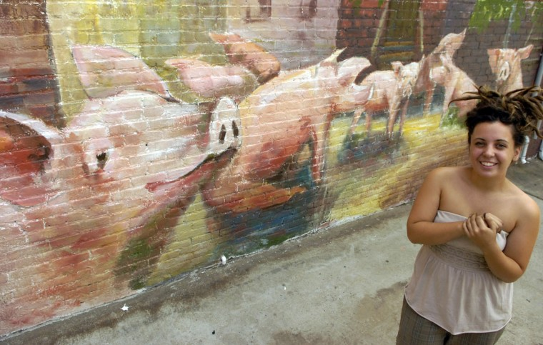 9/11/10: Pigtown artist Dominique Hellgeth, 22, poses next to a mural on Callender St. in Pigtown she completed two weeks prior to Pigtown Festival. Brian Krista/Baltimore Sun