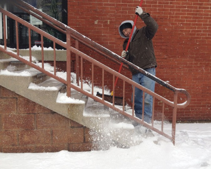 Scott Woodell sweeps snow off the steps at the Baltimore Community Resource Center on W. 25th Street near Maryland Ave. (Amy Davis / Baltimore Sun)