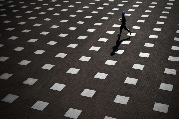 A man jogs in Yokohama, near Tokyo, Friday, Jan. 9, 2015. (AP Photo/Eugene Hoshiko)