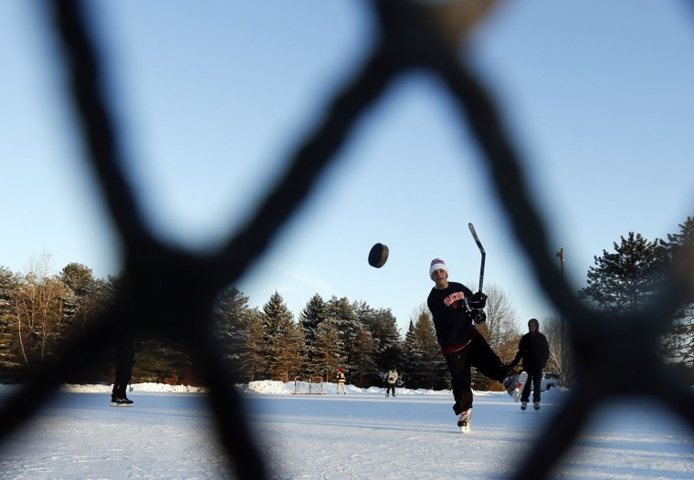 Anthony Zabielski takes a shot while playing ice hockey at Saratoga Spa State Park on Wednesday, Jan. 14, 2015, in Saratoga Springs, N.Y. (AP Photo/Mike Groll)