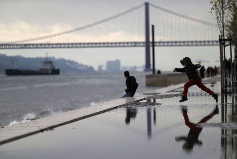 A young boy jumps over a puddle by the Tagus riverbank, in Lisbon, Sunday, Jan. 18, 2015. At the background is the April 25th bridge, whose name was given after the Carnations revolution that restored the democracy in Portugal in April 1974. (AP Photo/Francisco Seco)