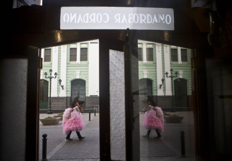 "Daysi Villavicencio rides on the back of a photographer's assistant to keep her gown from getting dirty as they're reflected in a mirror at the iconic Cordano Bar in Lima, Peru, Thursday, Jan. 22, 2015. Villavicencio is celebrating her 15th birthday and had a series of pictures made in her formal ""quinceanera"" gown. (AP Photo/Esteban Felix)"