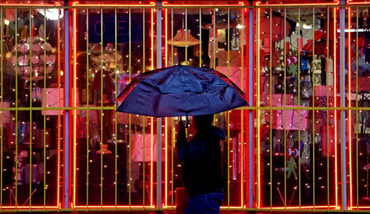 A pedestrian walks past Light Bulbs Unlimited during a recent rain shower along Westheimer Road, Thursday, Jan. 22, 2015, in Houston. (AP Photo/Houston Chronicle, Gary Coronado)