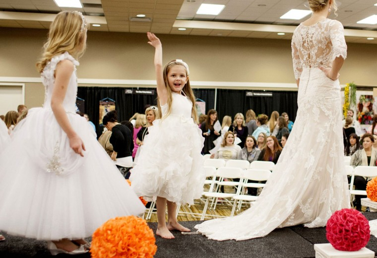 Six-year-old Delainey Seaton spots her parents and waves on Saturday, Jan. 24, 2015, during the Bristol Bridal Expo at the Julian Carroll Convention Center in Paducah, Ky. Seaton is shown in a dress from designer Tip Top from Anne's Bridals in West Paducah. (AP Photo/The Paducah Sun, John Paul Henry)