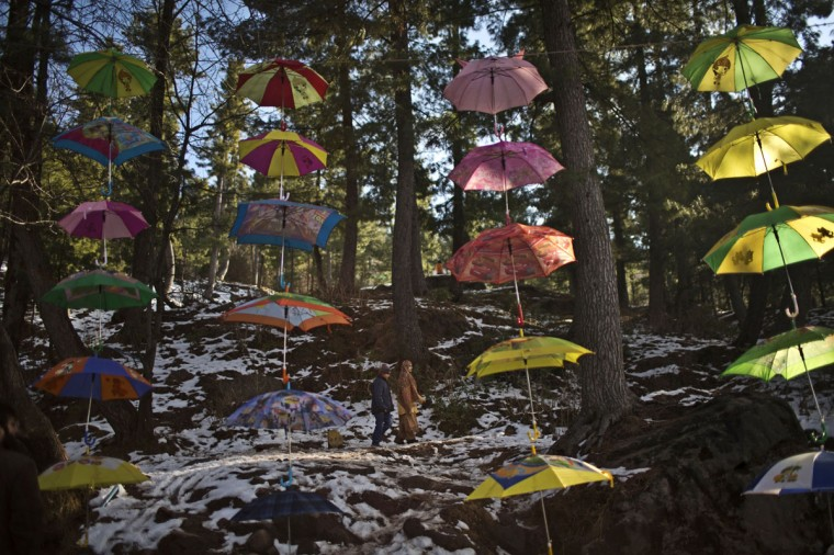 Umbrellas are displayed for sale by a Pakistani vendor on a roadside in Murree, Pakistan, Sunday, Jan. 25, 2015. (AP Photo/Muhammed Muheisen)