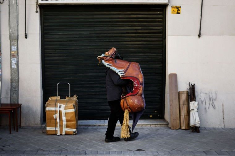 A man holds a cardboard toy horse for sale as he packs his portable shop after a street flea market in Madrid, Spain, Sunday, Jan. 25, 2015.(AP Photo/Daniel Ochoa de Olza)