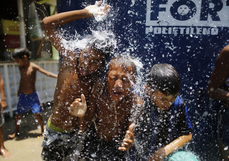 Children play under the water that they manage to spill over from a water tank, to cool off from the summer heat, at the Alemao Complex slum in Rio de Janeiro, Brazil, Thursday, Jan. 29, 2015. State Environment Secretary Andre Correa acknowledged the region is ìexperiencing the worst water crisis in its history,î but said water provisioning would continue as normal through July, even in the worst-case scenario of continued drought over the coming weeks and months. (AP Photo/Leo Correa)