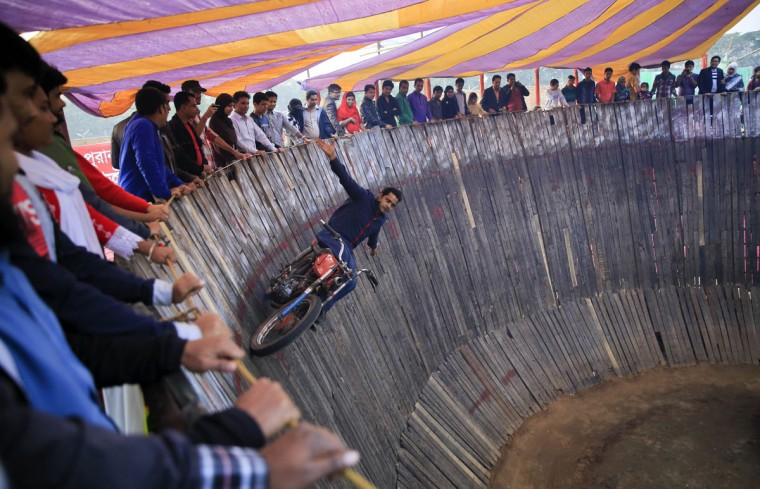 Bangladeshi daredevil S.M. Rashed performs inside a Well of Death at a trade fair in Dhaka, Bangladesh, Friday, Jan. 30, 2015. In the Well of Death, stunt drivers on motorbikes and cars drive in circles around the vertical walls of the well-shaped construction. (AP Photo/ A.M. Ahad)