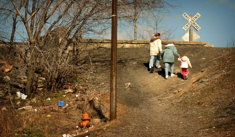 "3/3/06: From left: Karen Brown, 26, her mother, Jane Brown, 58, and Karen's daughter, Mallory Carnes, 3, take a shortcut at the end of Ostend St. on their way to the grocery store. The hill they are climbing used to be a dumping ground, and although some litter is still there, it is much better than it used to be. Karen Brown says, ""It does seem to be getting a little cleaner. I hate to be hopeful about it. I've lived here my whole life and you get the feeling it's never going to get better. Lately in different areas, there's been some improvement."".ÖWashington Village/Pigtown is an Environmental Benefits District, which means that the community received coordinated assistance from federal, state and local levels to address environmental issues, i.e. trash in the neighborhood. Lesley Smith, executive director of the Washington Village Pigtown Neighborhood Planning Council, helps coordinate efforts to clean up the community. Andre F. Chung/Baltimore Sun"