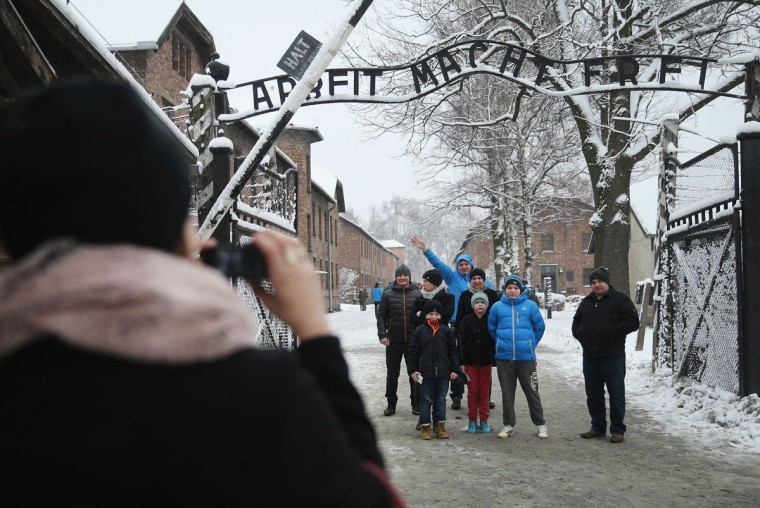 "Visitors snap a photo under the infamous ""Arbeit Macht Frei"" slogan, which literally translates to: ""Work Makes Free,"" at the former Auschwitz I concentration camp that today is a museum, on January 25, 2015 in Oswiecim, Poland. International heads of state, dignitaries and over 300 Auschwitz survivors will commemorate the 70th anniversary of the liberation of Auschwitz by Soviet troops in 1945 on January 27. Auschwitz was among the most notorious of the concentration camps run by the Nazis to ensalve and kill millions of Jews, political opponents, prisoners of war, homosexuals and Roma. (Photo by Sean Gallup/Getty Images)"