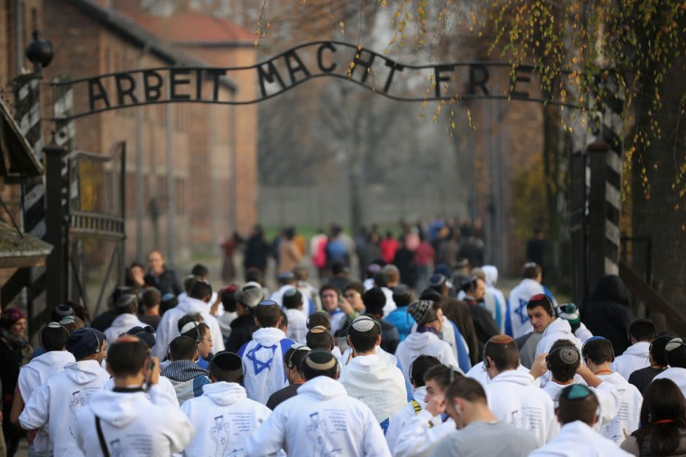 Young Israelis walk under the infamous German inscription that reads 'Work Makes Free' at the main gate of the Auschwitz I extermination camp on November 13, 2014 in Oswiecim, Poland. (Photo by Christopher Furlong/Getty Images)