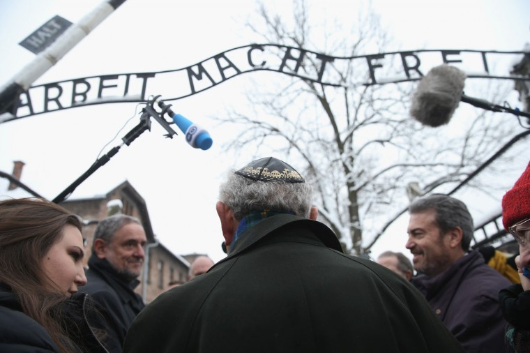 "Journalists surround an Auschwitz survivor at the notorious ""Arbeit Macht Frei"" entrance gate at the former Auschwitz I concentration camp, which is now a museum, on January 26, 2015 in Oswiecim, Poland. (Photo by Sean Gallup/Getty Images)"