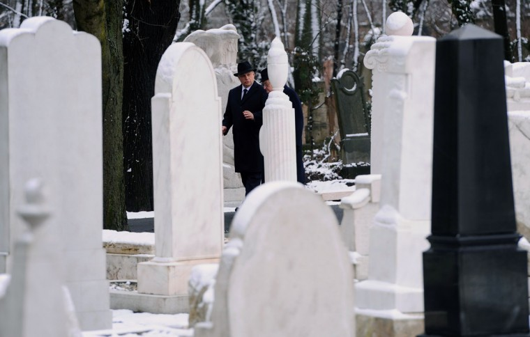 Hungarian Prime Minister Viktor Orban (left) chats with former PM Peter Boros (right) as they walk by renovated Jewish graves at the Kozma street Jewish cemetery in Budapest, on January 26, 2015 during a ceremony for the grave refurbishment on the eve of the 70th anniversary of the liberation of the Auschwitz death camp held by the Nazis during WWII. (ATTILA KISBENEDEK/AFP/Getty Images)