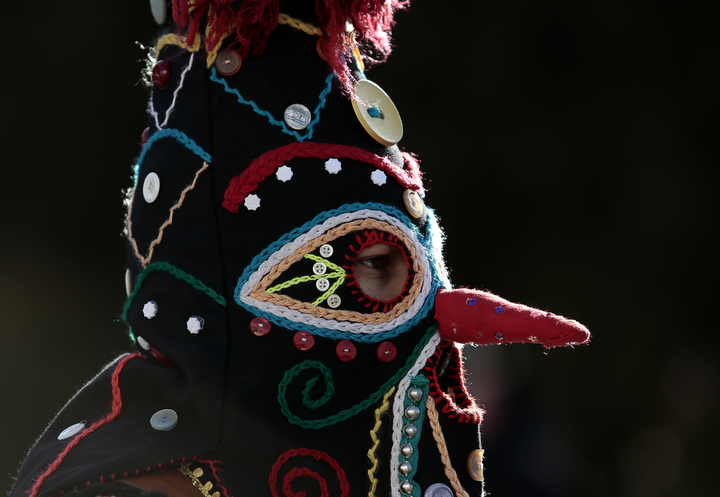 "A masked Bulgarian dancer takes part in the second competition day of the 24th International Festival of Masquerade Games ""Surva"" in the town of Pernik, Bulgaria. Some 5,000 people are expected to take part in the three-day festival devoted to an ancient Bulgarian pagan rite. Surva is performed by costumed men, some in sheepskin, or other colorful garments, bells and masks, who walk around and dance to scare away the evil spirits, in hope to provide a good harvest, health, fertility, and happiness. (Valentina Petrova/AP Photo)"