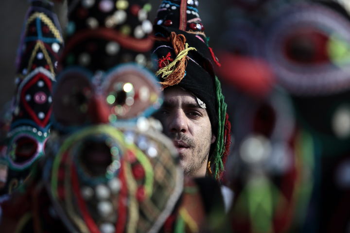 "A Bulgarian dancer is seen between masks as they take part in the second competition day of the 24th International Festival of Masquerade Games ""Surva"" in the town of Pernik, Bulgaria. Some 5,000 people are expected to take part in the three-day festival devoted to an ancient Bulgarian pagan rite. Surva is performed by costumed men, some in sheepskin, or other colorful garments, bells and masks, who walk around and dance to scare away the evil spirits, in hope to provide a good harvest, health, fertility, and happiness. (Valentina Petrova/AP Photo)"