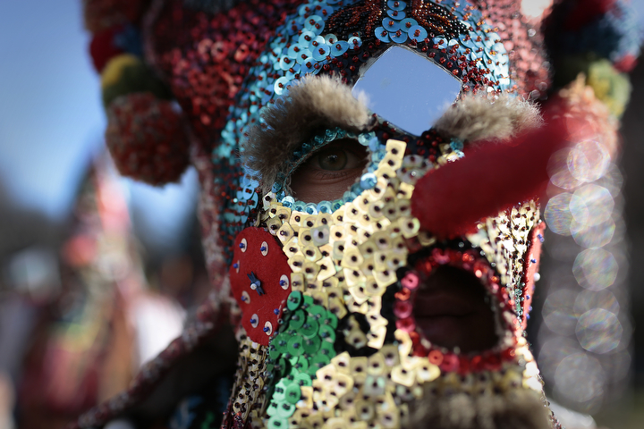 "A Bulgarian dancer looks on behind his mask as they take part in the second competition day of the 24th International Festival of Masquerade Games ""Surva"" in the town of Pernik, Bulgaria. Some 5,000 people are expected to take part in the three-day festival devoted to an ancient Bulgarian pagan rite. Surva is performed by costumed men, some in sheepskin, or other colorful garments, bells and masks, who walk around and dance to scare away the evil spirits, in hope to provide a good harvest, health, fertility, and happiness. (Valentina Petrova/AP Photo)"