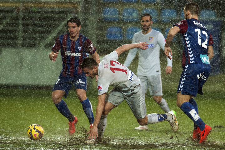 Atletico de Madrid's Saul Niguez, center, duels for the ball in heavy rain with SD Eibar's Borja, during their La Liga soccer match, at Ipurua stadium in Eibar, northern Spain, Saturday. (Alvaro Barrientos/AP Photo)