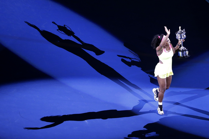 Serena Williams of the U.S., holding the trophy, casts a shadow on the court, after defeating Maria Sharapova of Russia in during their women's singles final at the Australian Open tennis championship in Melbourne, Australia. (Lee Jin-man/AP Photo)