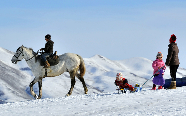 A boy rides a horse next to children sledding in the snow near the village of Prokhladnoe, some 20 km from Bishkek, as temperatures in the Chuy valley reached 10 C (50 F). (Vyacheslav Oseledko/AFP-Getty Images)