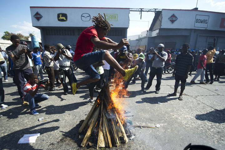 A demonstrator jump over a fire while performing a voodoo ceremony before a march against the government of Haitian President Michel Martelly in Port-au-Prince. Protesters marched through the streets calling for the resignation of the Haitian leader. (Hector Retamal/AFP-Getty Images)