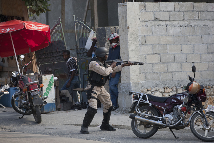 A National Police officer fires at protesters after clashes broke out with police during a demonstration to demand the resignation of President Michel Martelly, in Port-au-Prince, Haiti. The protest was the latest in a series of demonstrations demanding Martelly leave office before his term expires next year. (Dieu Nalio Chery/AP Photo)